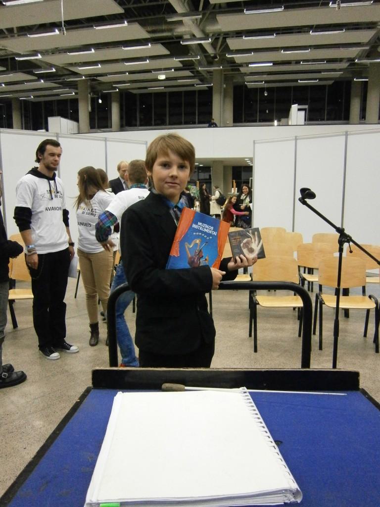 """Adomas Ragelis su laimėtais prizais: knyga """"Muzikos instrumentai vaikams"""" ir CD"""
