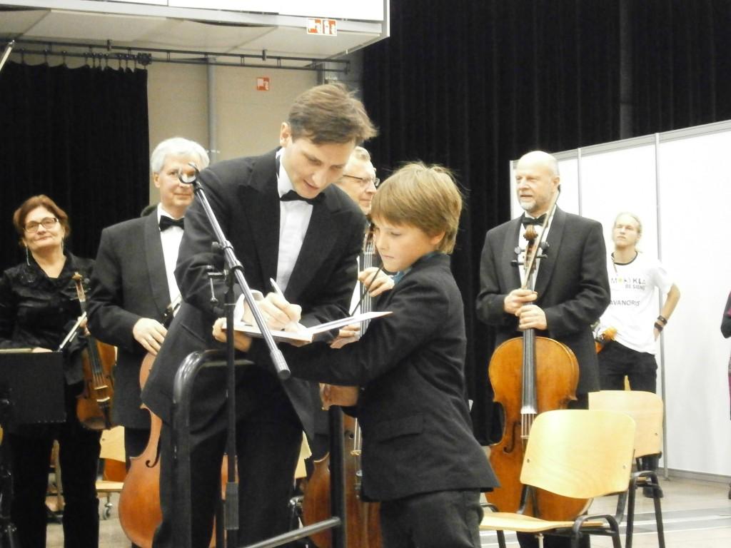 """Dirigentas Modestas Barkauskas pasirašo knygoje """"Muzikos instrumentai vaikams"""""""